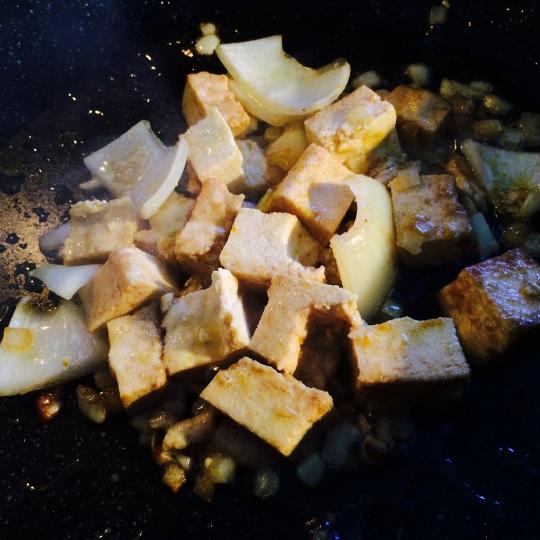 Stir fry tofu, onion and garlic.